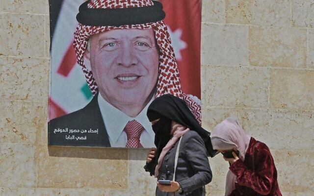 Women walk past a poster of Jordan's King Abdullah II on a street in the capital Amman, on April 6, 2021, after a security crackdown revealed tensions in the monarchy. (Khalil Mazraawi/AFP)