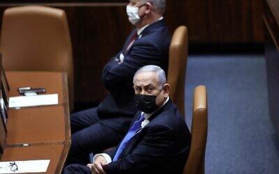 Prime Minister Benjamin Netanyahu (R) and Defense Minister Benny Gantz attend the swearing-in ceremony of Israel's Knesset (parliament) in Jerusalem, on April 6, 2021. (Alex Kolomoisky / POOL / AFP)