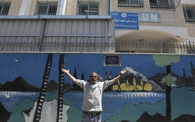 A Palestinian man gestures outside a United Nations health center in the Palestinian refugee camp of Jalazoun near Ramallah on April 8, 2021. (ABBAS MOMANI / AFP)