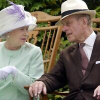 In this file photo taken on July 17, 2002 Britain's Queen Elizabeth II and Britain's Prince Philip, Duke of Edinburgh chat while seated during a musical performance in the Abbey Gardens, Bury St Edmunds, during her Golden Jubilee visit to Suffolk, east of England. (Fiona HANSON / POOL / AFP)
