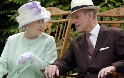 In this file photo taken on July 17, 2002, Britain's Queen Elizabeth II and Britain's Prince Philip, Duke of Edinburgh chat while seated during a musical performance in the Abbey Gardens, Bury St Edmunds, during her Golden Jubilee visit to Suffolk, east of England. (Fiona HANSON / POOL / AFP)