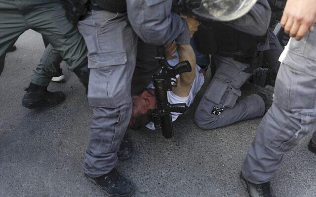 Israeli policemen detain MK Ofer Cassif, a Jewish member of the predominantly Arab Joint List electoral alliance, during a demonstration in Jerusalem's Sheikh Jarrah neighbourhood on April 9, 2021.  (AHMAD GHARABLI / AFP)