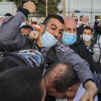A police officer scuffles with Ofer Cassif, a Jewish member of the predominantly Arab Joint List party, during a demonstration in East Jerusalem on April 9, 2021 (AHMAD GHARABLI / AFP)