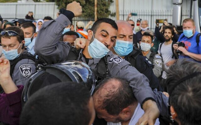 A police officer scuffles with Ofer Cassif, a Jewish member of the predominantly Arab Joint List electoral alliance, during a demonstration in East Jerusalem on April 9, 2021 (AHMAD GHARABLI / AFP)