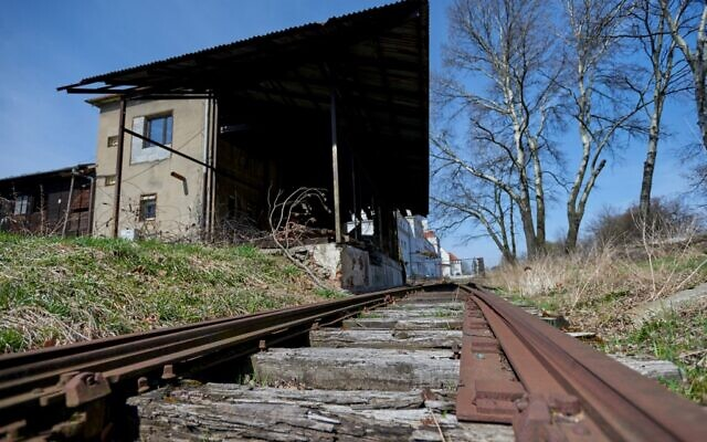 Pld train tracks leading past a former canteen building of SS guards at the former Nazi death camp Auschwitz-Birkenau, in Oswiecim, Poland, April 9, 2021 (BARTOSZ SIEDLIK / AFP)