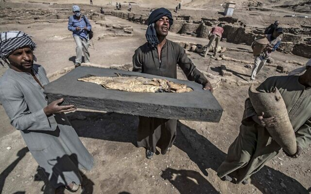 A picture taken on April 10, 2021, shows workers carrying a fish covered in gold uncovered at the archaeological site of a 3,000 year old city, dubbed The Rise of Aten, dating to the reign of Amenhotep III, uncovered by the Egyptian mission near Luxor (Khaled DESOUKI / AFP)