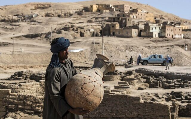 A picture taken on April 10, 2021, shows a worker carrying a pot at the archaeological site of a 3,000 year old city, dubbed The Rise of Aten, dating to the reign of Amenhotep III, uncovered by the Egyptian mission near Luxor (Khaled DESOUKI / AFP)