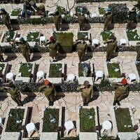 This picture taken on April 13, 2021, on Yom HaZikaron (Israel's Memorial Day) shows an aerial view of female Israeli soldiers performing salutes by graves at the Kiryat Shaul military cemetery in the Mediterranean coastal city of Tel Aviv. (JACK GUEZ / AFP)