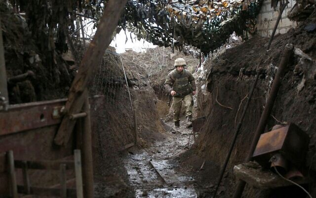 A Ukrainian serviceman walks along a trench at a position on the frontline with Russia-backed separatists near Gorlivka, Donetsk region, on April 14, 2021. (STR / AFP)
