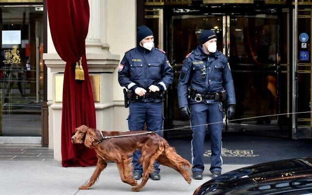 A dog passes by policemen guarding the entrance to the Grand Hotel Wien during the closed-door nuclear talks with Iran in Vienna on April 16, 2021, where diplomats of the EU, China, Russia and Iran hold their talks. (JOE KLAMAR / AFP)