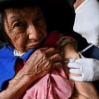 Indigenous nurse of the Misak ethnic group Anselmo Tunubala, 49, inoculates an elderly indigenous woman with a Sinovac vaccine against COVID-19 in the Guambia indigenous reservation, rural area of Silvia, department of Cauca, Colombia, on April 15, 2021 (Luis ROBAYO / AFP)