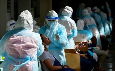 A medical worker wearing PPE (personal protective equipment) takes a swab sample from a woman during a mass testing event at a sport complex in Bangkok on April 17, 2021, after the recent outbreak of coronavirus cases in Thailand. (Mladen ANTONOV / AFP)