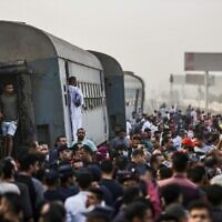 People gather by an overturned train carriage at the scene of a railway accident in the city of Toukh in Egypt's central Nile Delta province of Qalyubiya on April 18, 2021. (Ayman AREF / AFP)
