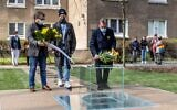 Participants lay a wreath and flowers in front of a monument dedicated to the underground archives of the Jewish ghetto, during its unveiling ceremony at the site where the Ringelblum Archive was hidden during Nazi occupation during the Second World War, in Warsaw, on April 19, 2021. (Wojtek RADWANSKI/AFP)