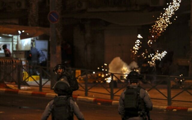 Palestinian run from stun grenades canisters as members of Israeli security forces deploy amid clashes with Palestinian protesters outside Damascus Gate in Jerusalem's Old City on April 22, 2021. (Photo by AHMAD GHARABLI / AFP)