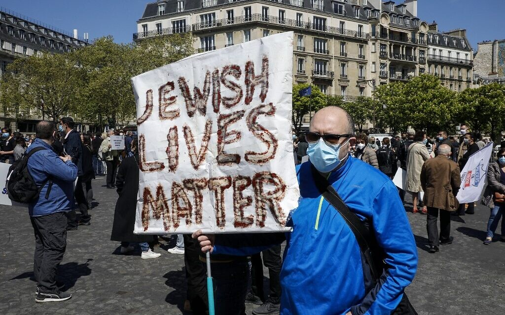 A man holds a placard as people gather to ask justice for late Sarah Halimi on Trocadero plaza in Paris on April 25, 2021. (Photo by GEOFFROY VAN DER HASSELT / AFP)