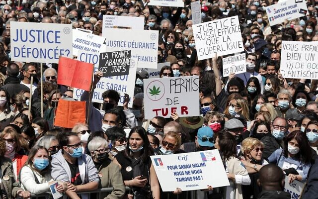 People hold placards reading 'Stoned justice?' (L), 'License to kill' (C) and 'A justice as efficient as the Super League' (R) as they gather to demand justice for Sarah Halimi, a slain French woman, on Trocadero plaza in Paris on April 25, 2021.(GEOFFROY VAN DER HASSELT / AFP)