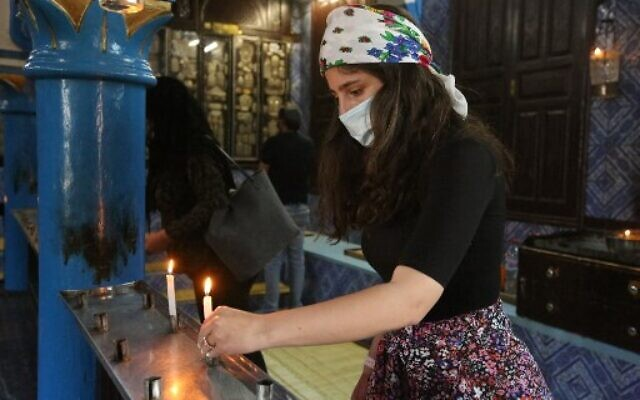 A Jewish pilgrim lights a candle on the first day of the annual pilgrimage to the Ghriba Synagogue, the oldest Jewish monument built in Africa, on April 26, 2021 in the Mediterranean Tunisian resort island of Djerba (Photo by FATHI NASRI / AFP)