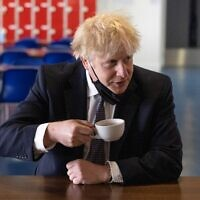 Britain's Prime Minister Boris Johnson, holds a cup of coffee as he speaks with pupils after taking part in a science lesson at King Solomon Academy in London, on April 29, 2021. (Dan Kitwood / POOL / AFP)