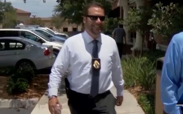 Joel Greenberg, bearing his tax collector badge and a sidearm, appears in a TV news report about his legal troubles in Seminole County, Florida, Jan. 25, 2021. (YouTube via JTA)