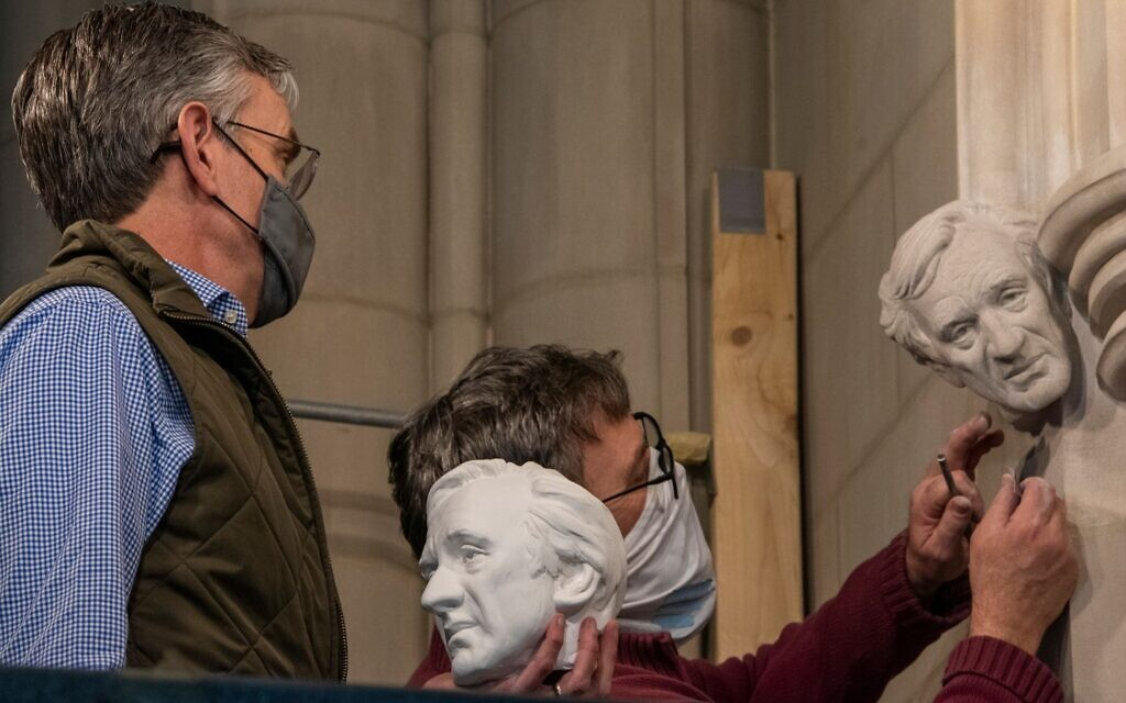 In this undated photo, sculptor Chas Fagan, left, holds a clay model of a bust of Elie Wiesel and watches as stonemason Sean Callahan, right, uses medieval techniques to carve the bust into the walls of the National Cathedral in Washington DC. (National Cathedral/ via JTA)