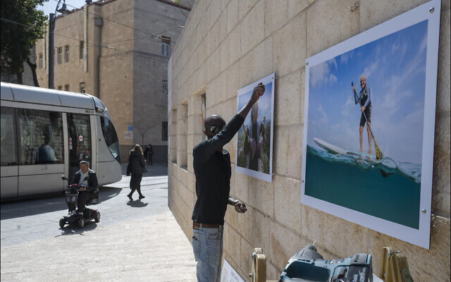 Hanging photographic portraits of Holocaust survivors that are part of The Lonka Project being exhibited in Safra Square in Jerusalem, opening April 8, 2021, Yom HaShaoh, Israeli Heroes and Martyrs remembrance  day, and will run for four months, until at least August 2021 (Courtesy The Lonka Project)
