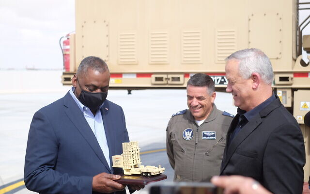 Defense Minister Benny Gantz, right, and Israeli Air Force chief Amikam Norkin, center, give US Defense Secretary Lloyd Austin a model of the Iron Dome missile defense system at the Nevatim Air Base in southern Israel on April 12, 2021. (Judah Ari Gross/Times of Israel)