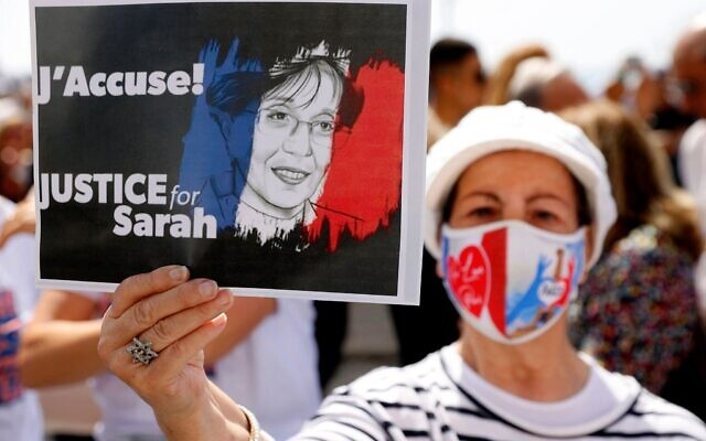 A woman holds up a sign during the day of rallies around the world protesting the French judicial system's handling of the Sarah Halimi case, April 25, 2021. (Jack Guez/AFP/Getty Images/ via JTA)
