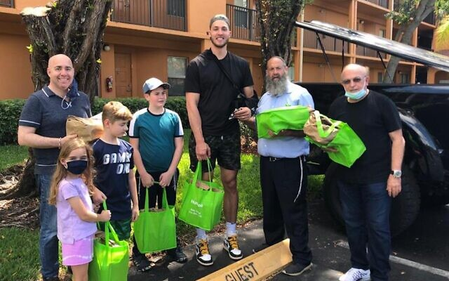 Meyers Leonard, center, distributes Passover dinners to Holocaust survivors and Jewish seniors in the Miami area with the help of Rabbi Pinny Andrusier, second from right. (Chabad of Southwest Broward via JTA)
