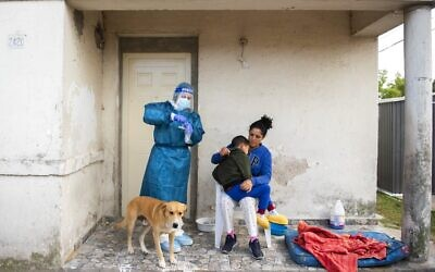 A healthcare worker prepares the material to test a child for COVID-19, on the outskirts of Montevideo, Uruguay, March 18, 2021. (AP Photo/Matilde Campodonico)