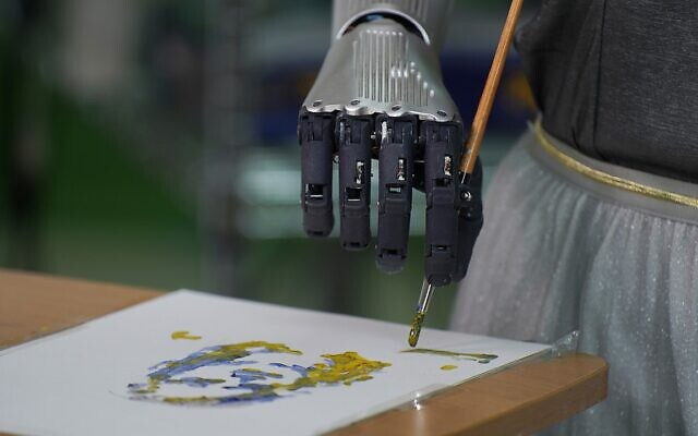 Robot Sophia uses a brush to paint at Hanson Robotics studio in Hong Kong on March 29, 2021 (AP Photo/Vincent Yu)