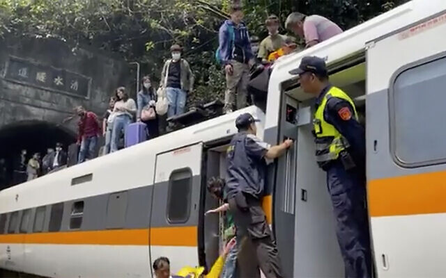 In this image made from a video released by hsnews.com.tw, passengers are helped to climb out of a derailed train in Hualien County in eastern Taiwan, April 2, 2021. (hsnews.com.tw via AP)