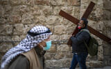 A Christian carries a cross as he walks along the Via Dolorosa towards the Church of the Holy Sepulchre, traditionally believed by many to be the site of the crucifixion of Jesus during the Good Friday procession in Jerusalem's Old City, April 2, 2021. (AP Photo/Ariel Schalit)