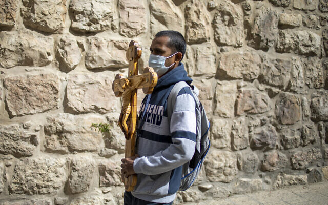 A Christian carries a cross along the Via Dolorosa towards the Church of the Holy Sepulchre, traditionally believed by many to be the site of the crucifixion of Jesus during the Good Friday procession in Jerusalem's Old City, April 2, 2021. (AP Photo/Ariel Schalit)