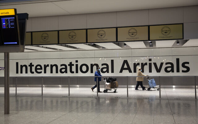 Illustrative: Arriving passengers walk past a sign in the arrivals area at Heathrow Airport in London, Jan. 26, 2021. (Matt Dunham/AP)