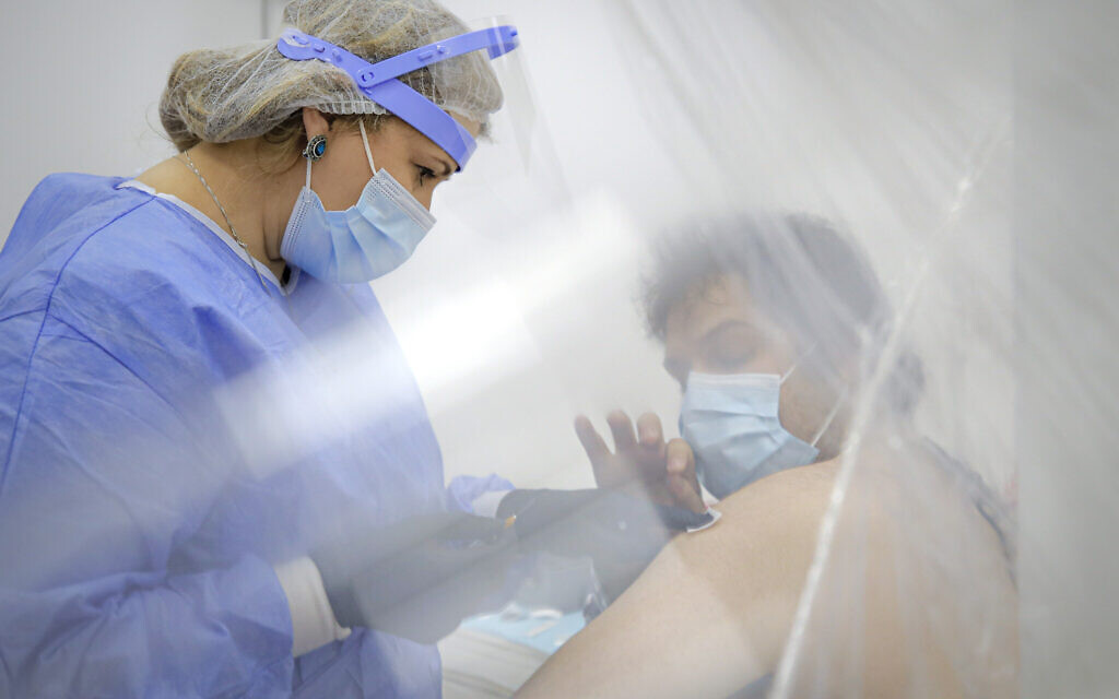 A man seen through plastic sheets gets a bandaid applied on his arm by a member of the medical staff after getting an AstraZeneca vaccine at a vaccination center in Bucharest, Romania, Wednesday, April 7, 2021.(AP Photo/Vadim Ghirda)