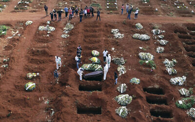 In this April 7, 2021, file photo, cemetery workers wearing protective gear lower the coffin of a person who died from complications related to COVID-19 into a gravesite at the Vila Formosa cemetery in Sao Paulo, Brazil. (AP/Andre Penner, File)