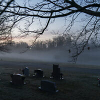 In this Wednesday, March 17, 2021 file photo, morning fog blankets a cemetery in West Virginia. The number of U.S. suicides fell nearly 6% in 2020 amid the coronavirus pandemic — the largest annual decline in at least four decades, according to preliminary government data. (AP Photo/David Goldman)