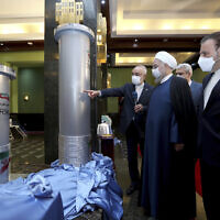 In this photo released by the official website of the office of the Iranian Presidency, President Hassan Rouhani, second right, listens to head of the Atomic Energy Organization of Iran Ali Akbar Salehi while visiting an exhibition of Iran's new nuclear achievements in Tehran, Iran, Saturday, April 10, 2021. (Iranian Presidency Office via AP)