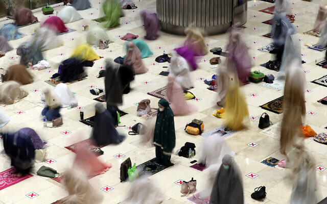 "In this photo taken using slow shutter speed, Muslim women offer an evening prayer called ""taraweeh"" marking the first eve of the holy fasting month of Ramadan at Istiqlal Mosque in Jakarta, Indonesia. April 12, 2021. (AP Photo/ Achmad Ibrahim)"