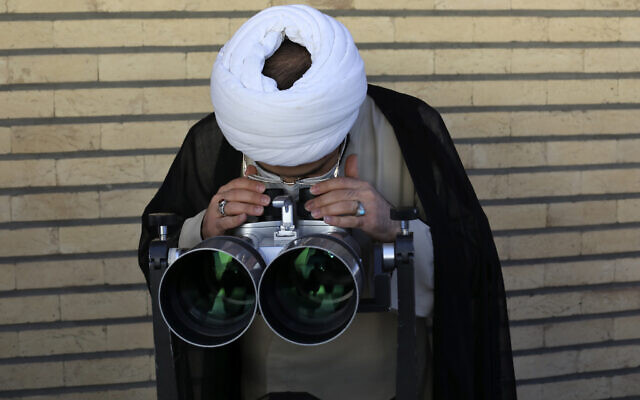 A clergyman searches the sky with a telescope for the new moon that signals the start of the Islamic holy fasting month of Ramadan, at the Imam Ali observatory about 28 miles (45 kilometers) outside the holy city of Qom, south of the capital Tehran, Iran, April 13, 2021. (AP Photo/Vahid Salemi)