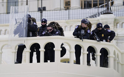 Police keep a watch on demonstrators who tried to break through a police barrier at the Capitol in Washington, January 6, 2021. (AP Photo/Julio Cortez, File)