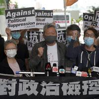 Pro-democracy activist Lee Cheuk-yan, center, arrives at a court in Hong Kong Friday, April 16, 2021. (AP Photo/Kin Cheung)
