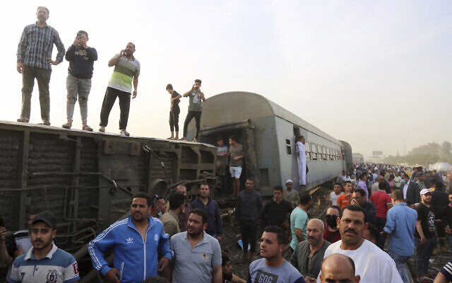 People gather at the site where a passenger train derailed, injuring at least 100 people, in Banha, Qalyubia province, Egypt, on April 18, 2021. (AP Photo/Fadel Dawood)