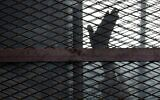 A member of the Muslim Brotherhood waves his hand from a defendants cage in a courtroom in Torah prison, southern Cairo, Egypt, August 22, 2015. (AP Photo/Amr Nabil, File)