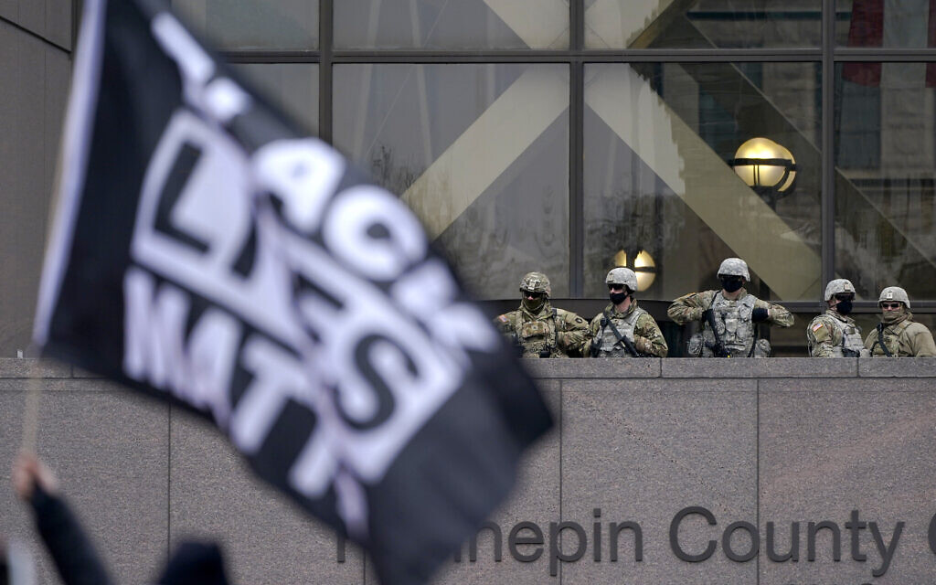 National Guard members are seen as a person flies a Black Lives Matter flag during a rally outside of the Hennepin County Government Center in Minneapolis on Monday, April 19, 2021, after the murder trial against former Minneapolis police Officer Derek Chauvin advanced to jury deliberations. (AP Photo/Julio Cortez)