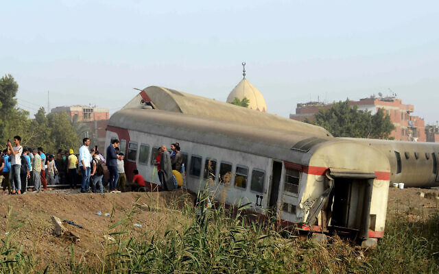 People gather at the site where a passenger train derailed killing at least 11 people and injuring at least 98 others, near Banha, Qalyubia province, Egypt. (AP Photo/Tarek Wagih, File)