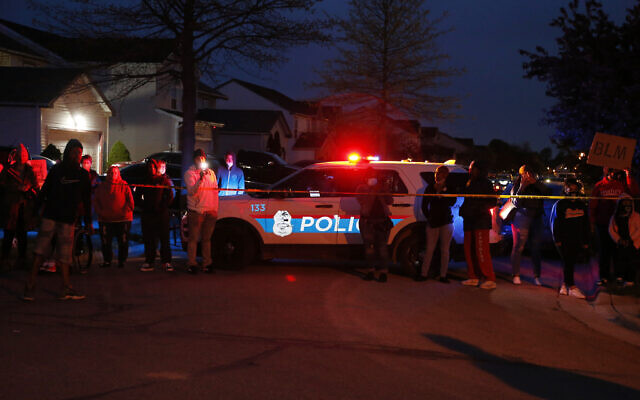 A crowd gathers to protest in the neighborhood where a Columbus police officer fatally shot a teenage girl who appeared to be trying to stab others, April 20, 2021, in Columbus, Ohio. (AP Photo/Jay LaPrete)