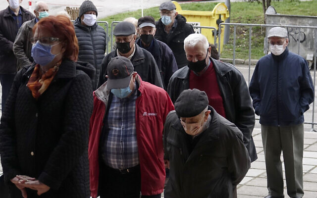 People wait for a COVID-19 vaccine, outside a sports hall in the capital Sarajevo, Bosnia, Wednesday, April 21, 2021. (AP Photo/Eldar Emric)