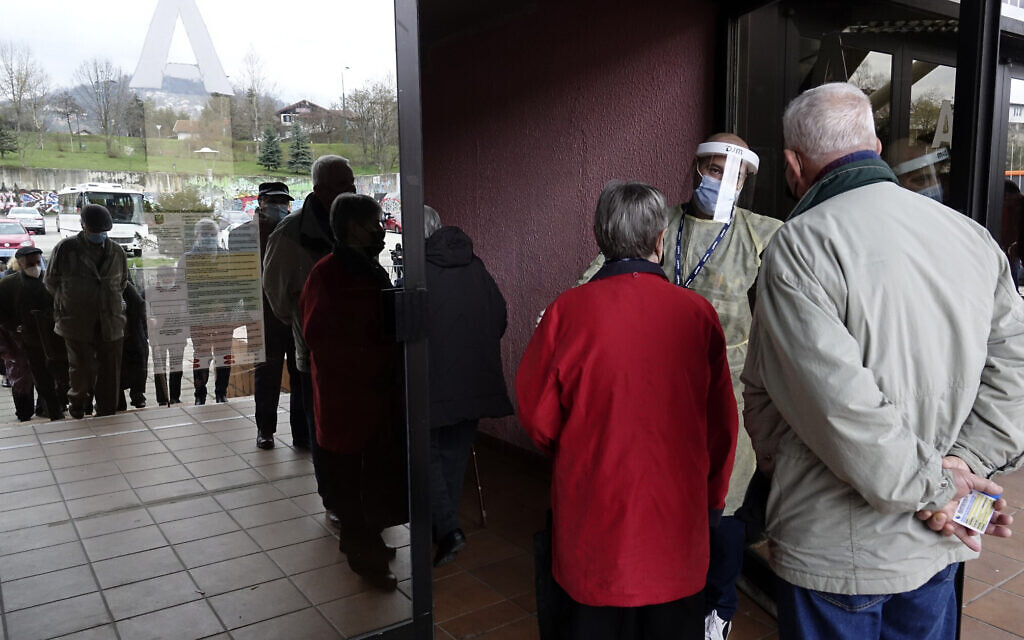 People wait for a COVID-19 vaccine at a sports hall in the capital Sarajevo, Bosnia, Wednesday, April 21, 2021. (AP Photo/Eldar Emric)